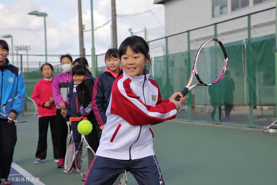 硬式テニスの競技体験。当日は本学の部活動生がコーチ役となり指導しました。