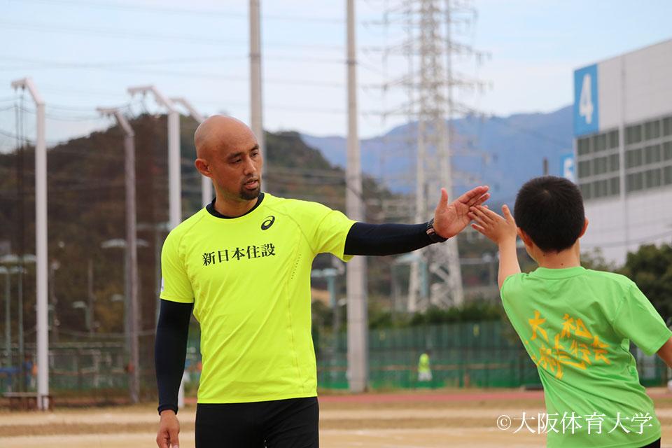 参加者とハイタッチする山本篤選手