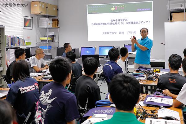 大学内の石川研究室に招かれた高校生たちは、先生の解説に真剣な面持ちで聴講